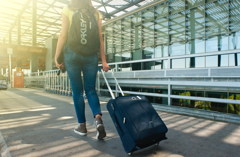 woman walking with luggage pexels