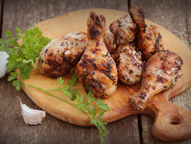 Grilled chicken legs on cutting board istock
