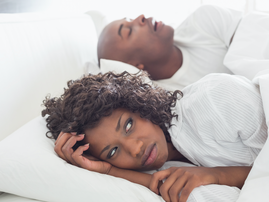 nnoyed woman lying in bed with snoring boyfriend / iStock