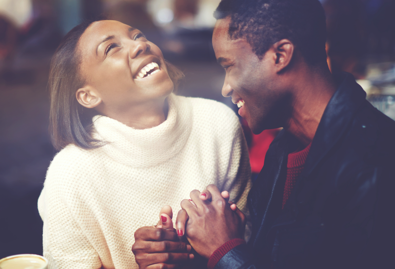 Young happy man and woman laughing together / iStock