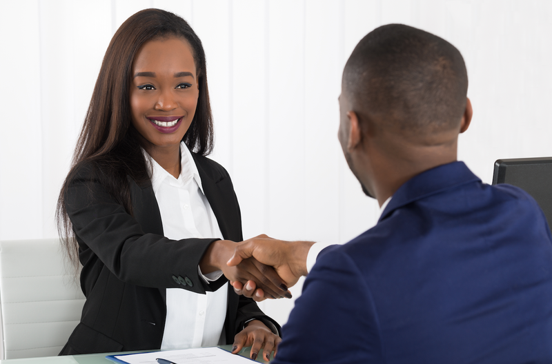 Two Businesspeople Shaking Hands At Office / iStock