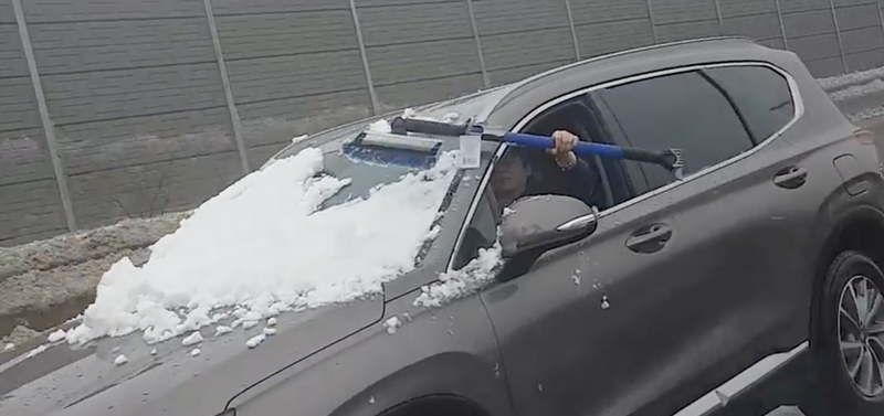 Woman tries to brush snow off her windshield while driving blind