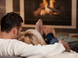 Couple cuddling on couch / iStock