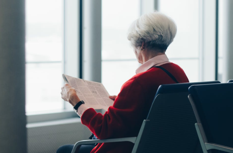 Elderly woman reading newspaper / Pexels