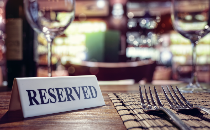 Reserved sign on restaurant table with bar background / iStock
