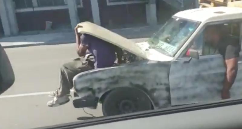 Man works on moving car engine