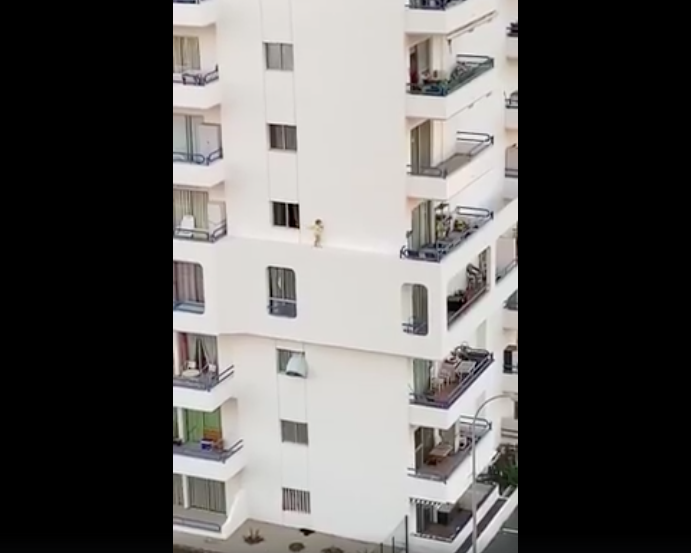 Young girl walking on ledge of wall