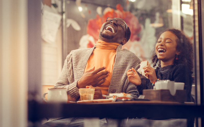 Father and daughter laughing out loud feeling happy together / iStock
