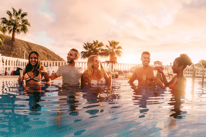 Happy friends drinking champagne in pool party at sunset / iStock