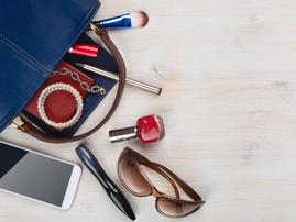 View on women bag stuff with copyspace on wooden background / iStock