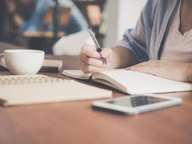 Businesswoman writing in a book / Pexels