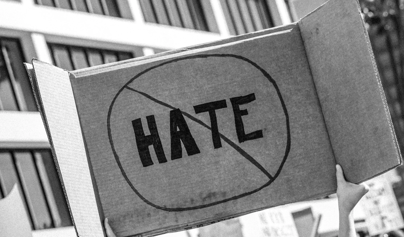 "A woman declares ""No Hate"" at a protest / Unsplash"