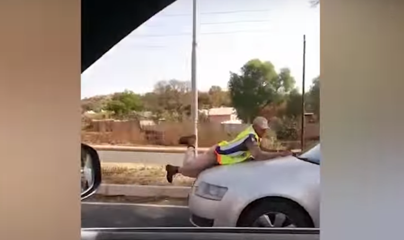 'Motorist drives off with officer on bonnet' / YouTube
