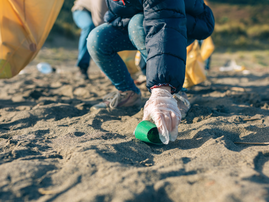 Little girl cleaning the beach / iStock