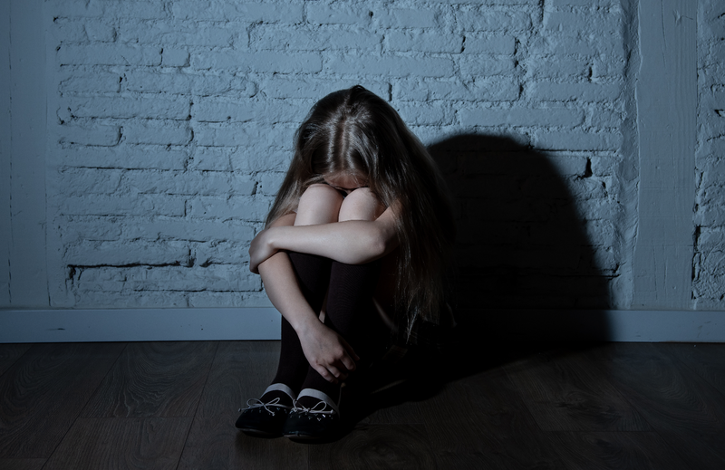 Girl crying in a corner / iStock