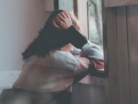 Sad woman by door / Pexels