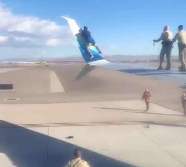 Unruly man climbs onto airplane wing before takeoff