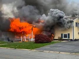woman sitting outside burning house