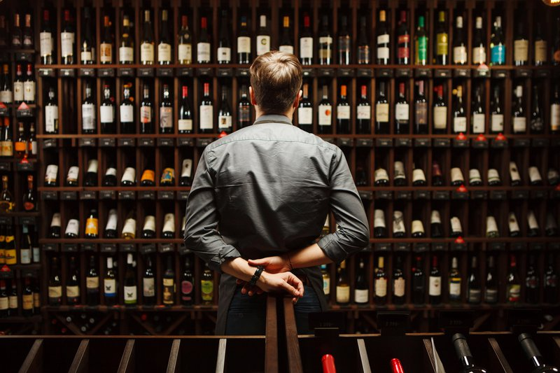 Man standing in front of wine cellar