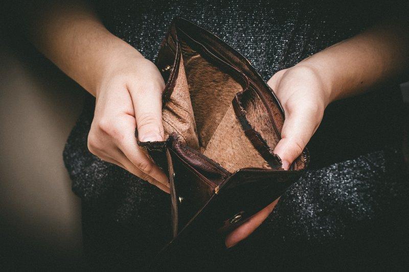 Woman holding empty wallet