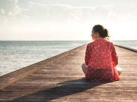Woman sitting on pier beach