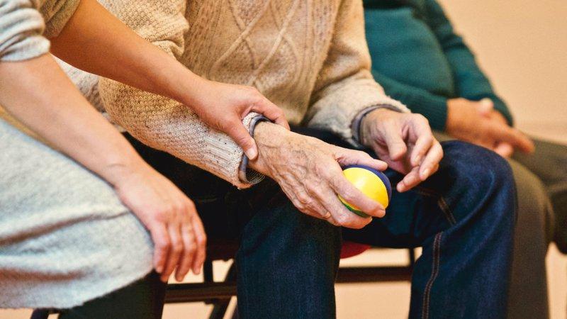 woman holds elderly man's arm