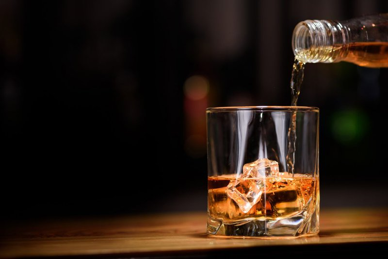 Man pouring whiskey in to glass/ iStock