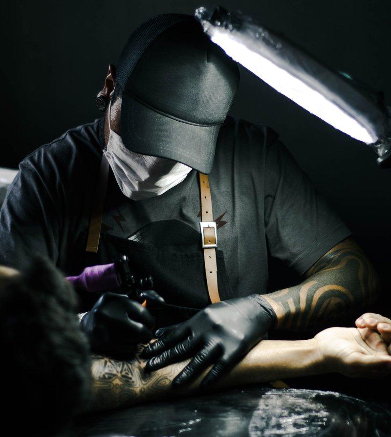 man tattooing arm/pexels