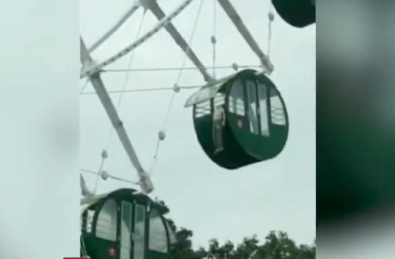 boy hangs from ferris wheel