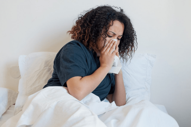 Woman cold flu sick in bed