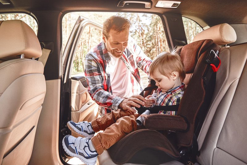Father putting child in car seat
