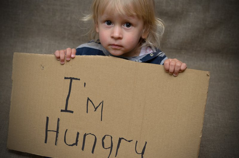 Child holding 'I'm hungry' board