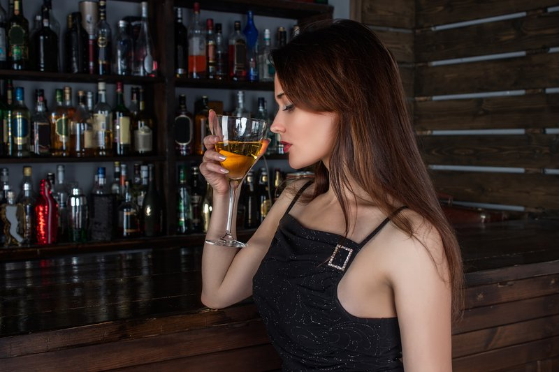 woman in black drinks cocktail