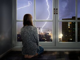 Girl looking through window during thunderstorm