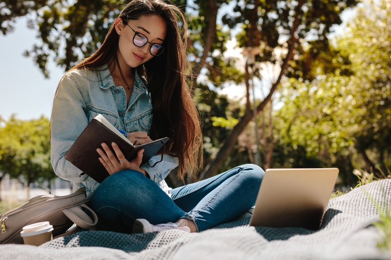 Young woman studying sitting outdoors