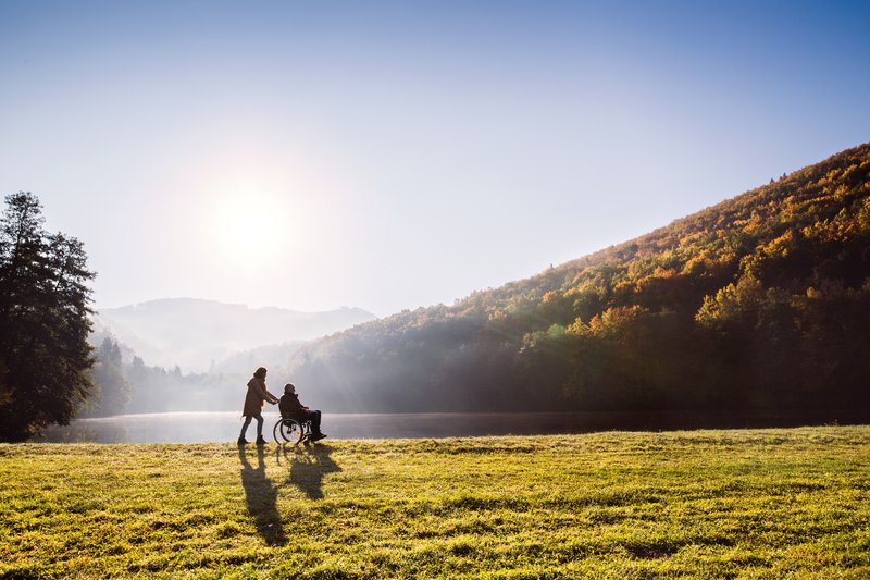 Senior couple with wheelchair in autumn nature. stock photo