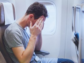 Headache in the airplane, man passenger afraid and feeling bad during flight, fear