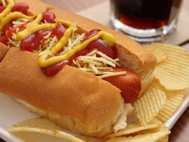 Delicious hot dog with ketchup, mustard and chips / iStock