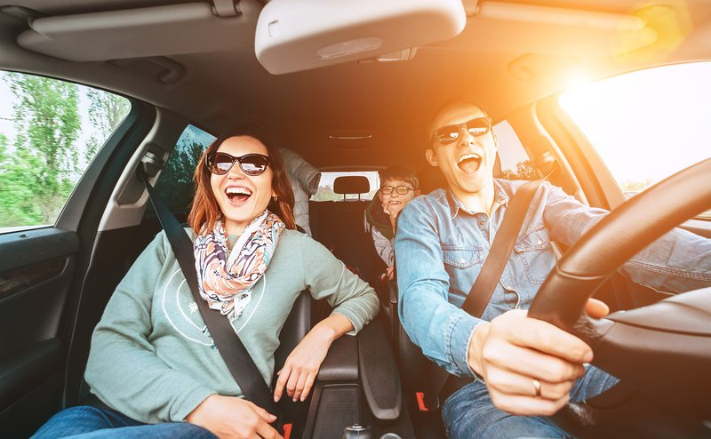 Cheerful young traditional family has a long auto journey and singing aloud the favorite song together. Safety riding car concept wide angle view image. stock photo