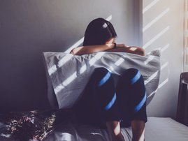 Sad, depressed woman in bed