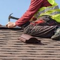 Two skilled roofer in special work wear with helmet in hands installing asphalt shingle or roof tile