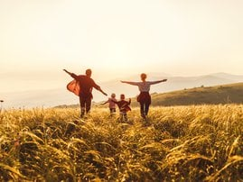 Happy family: mother, father, children son and daughter runing and jumping on sunset stock photo