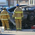 Two rescue professionals evaluating car accident