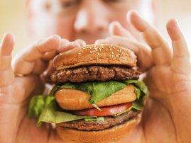 obese person eating hamburger