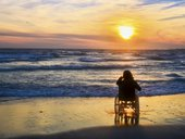 Sunset, makes sightseeing on the beach a woman on wheelchair stock photo