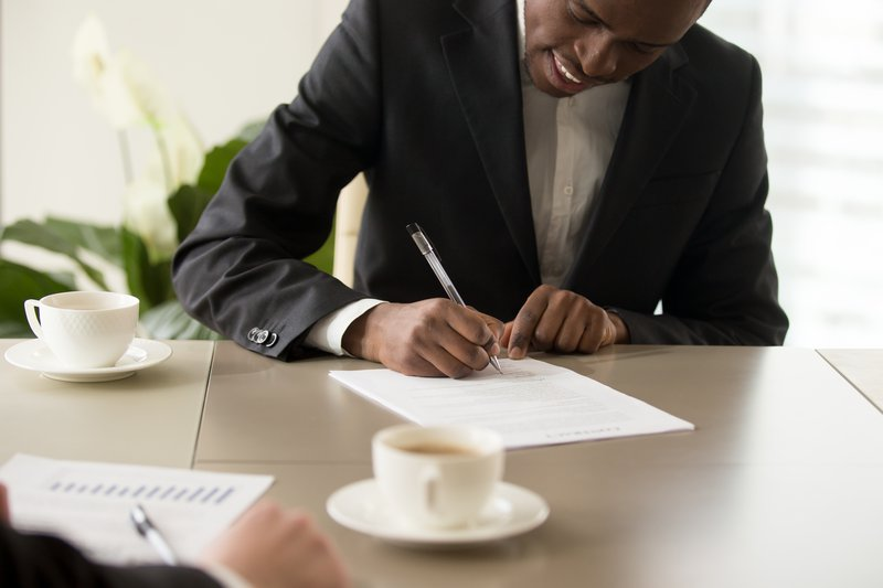 Man signing documentation / iStock