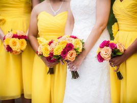 Bride Holding Bouquet with Bridesmaids / iStock