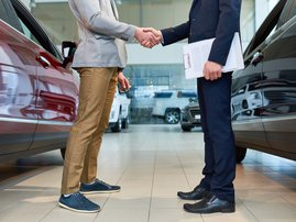 People Shaking Hands in Car Showroom