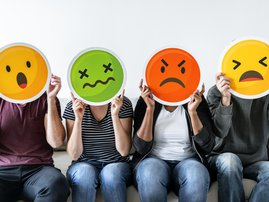 Diverse people holding emoticon / iStock