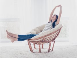 Good day! Happy cute pretty woman lying in the armchair on the weekend and stretching